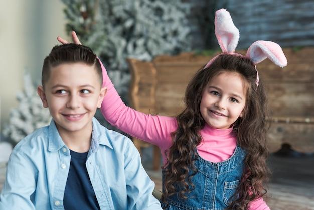 Menina, em, orelhas bunny, fazendo, chifres, com, dedos, para, menino