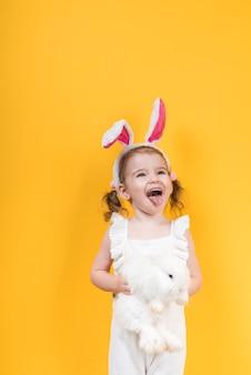 Menina em orelhas de coelho com coelho mostrando a língua
