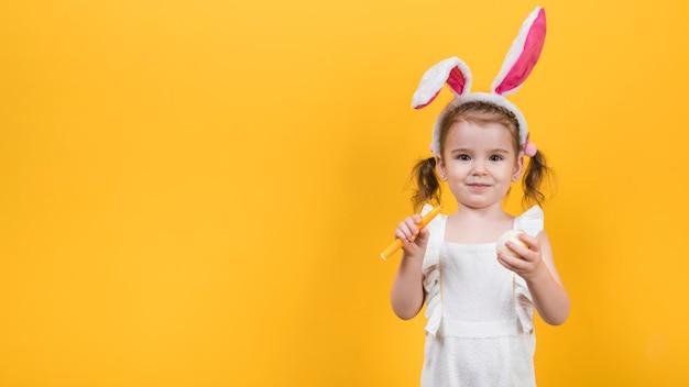 Menina em orelhas de coelho com ovo e caneta de feltro