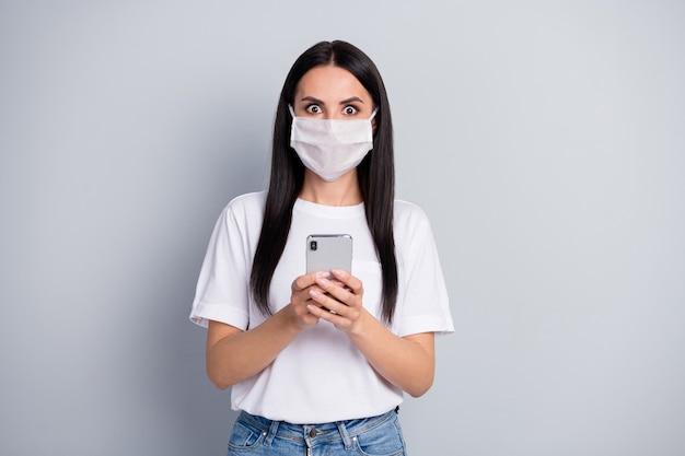 Menina em pânico, preocupada e atônita, usando máscara respiratória, usar telefone celular, ler notícias de redes sociais, impressionar corona vírus pandemia infecção vestir camiseta jeans jeans isolado fundo de cor cinza