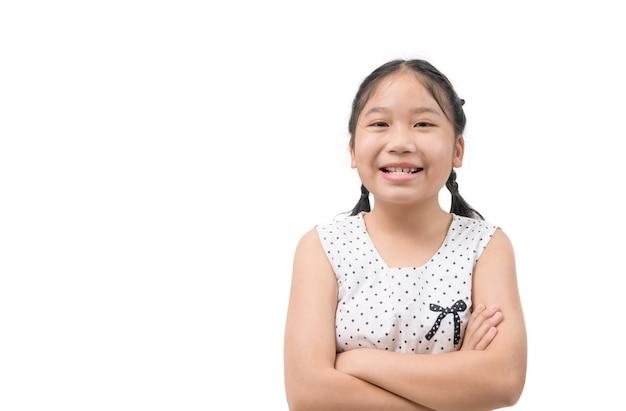 Menina em pé com os braços cruzados e sorrindo, isolado no fundo branco.