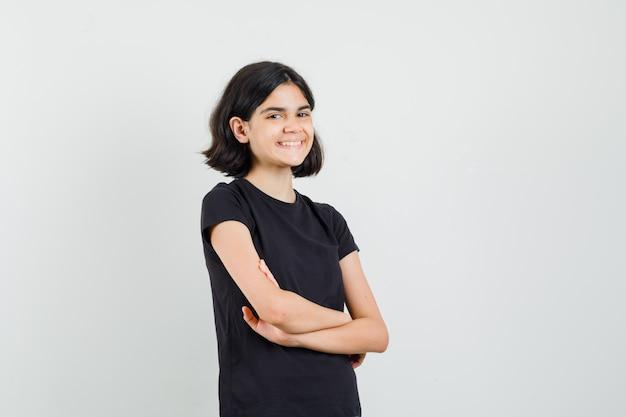 Menina em pé com os braços cruzados em uma camiseta preta e olhando alegre, vista frontal.