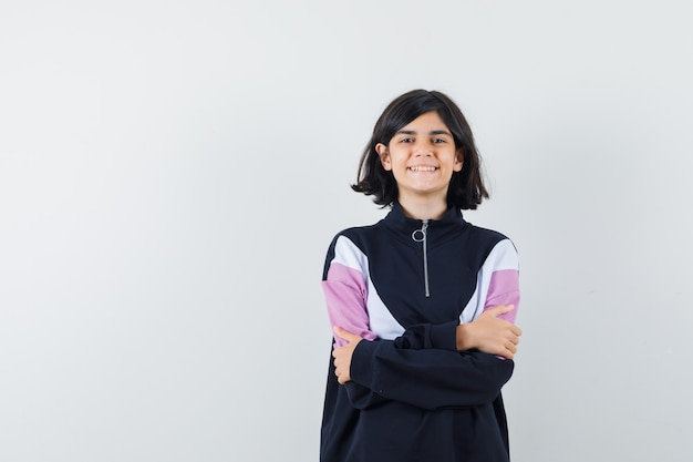 Menina em pé com os braços cruzados na camisa e parecendo orgulhosa. vista frontal.