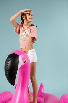 Menina em pé em um flamingo inflável
