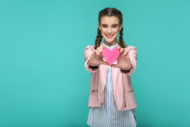 Menina em pé, mostrando a forma de um coração rosa e olhando para a câmera com um sorriso cheio de dentes