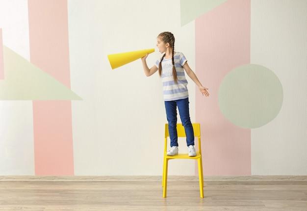 Menina em pé na cadeira gritando no megafone de papel dentro de casa