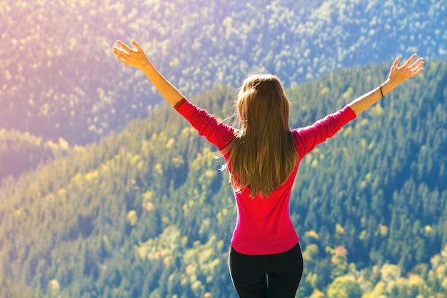 Menina em pé nas montanhas, levantando as mãos.