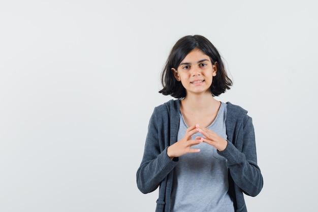 Menina em pé pensando em pose de camiseta, jaqueta e aparência sensata