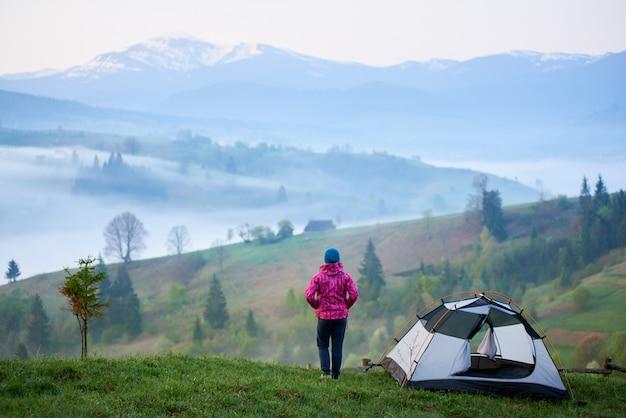 Menina em pé perto da barraca do turista em uma colina gramada