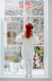 Menina em pé perto da janela grande
