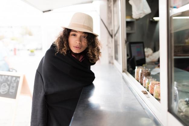 Menina em petiscos de compra da manta preta no caminhão do alimento.
