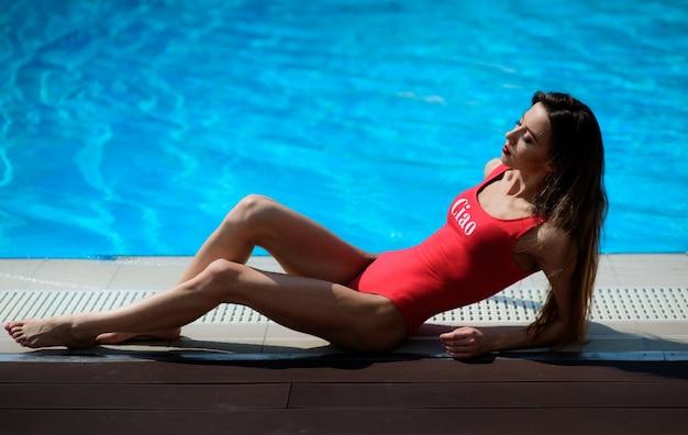Menina em roupa de banho vermelha está de uma piscina azul