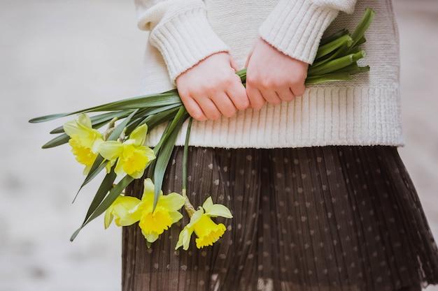 Menina em roupas pastel segurando narcisos amarelos, foco seletivo