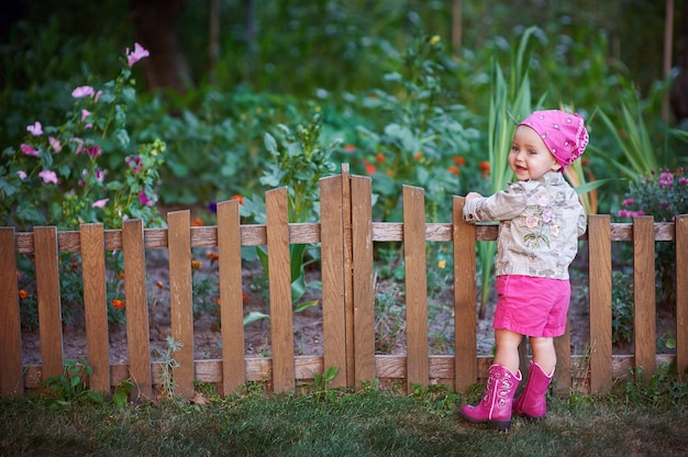 Menina em sapatos rosa perto da cerca