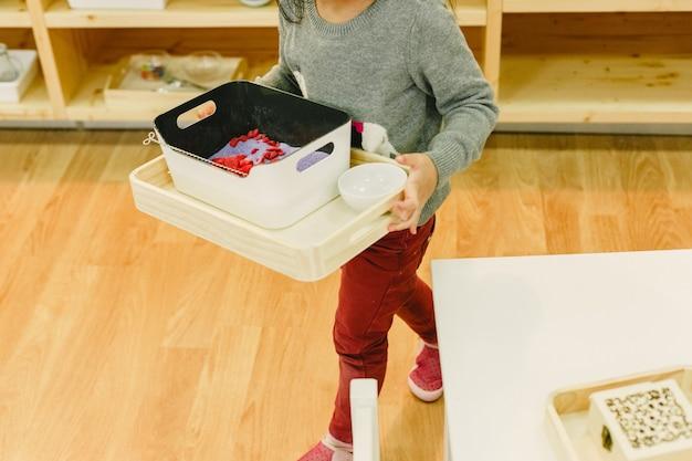 Menina em sua escola montessori movendo bandejas com material