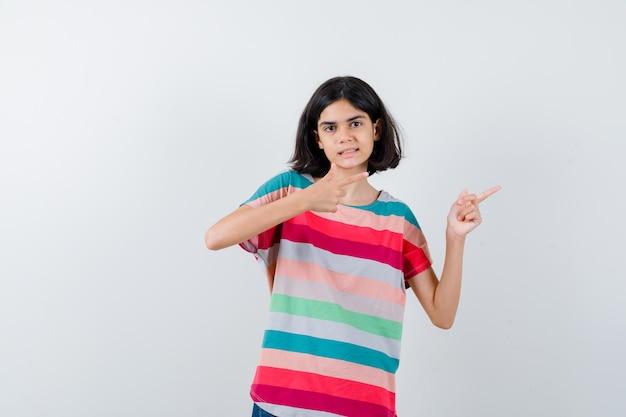Menina em t-shirt apontando para o lado direito e olhando alegre, vista frontal.