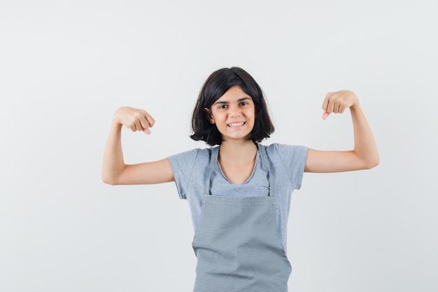 Menina em t-shirt, avental, mostrando os músculos dos braços e orgulhoso, vista frontal.