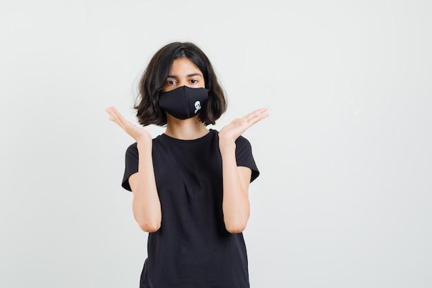 Menina em t-shirt preta, máscara de mãos dadas perto do rosto, vista frontal.
