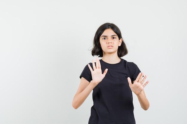 Menina em t-shirt preta mostrando gesto de recusa e parecendo irritada, vista frontal.