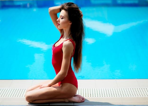 Menina em terno vermelho senta com piscina azul