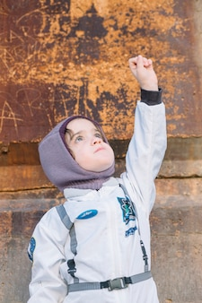 Menina em traje espacial de pé com mão acima