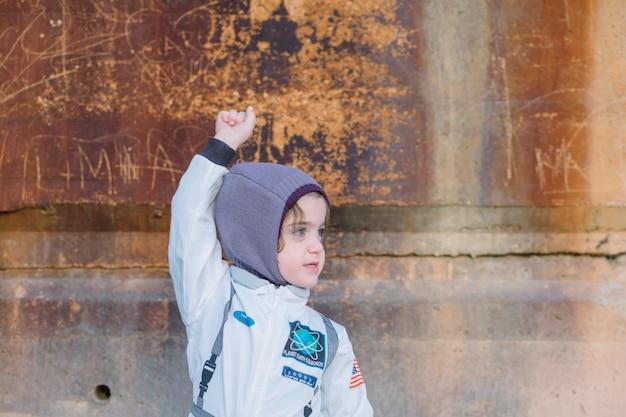 Menina em traje espacial na parede velha