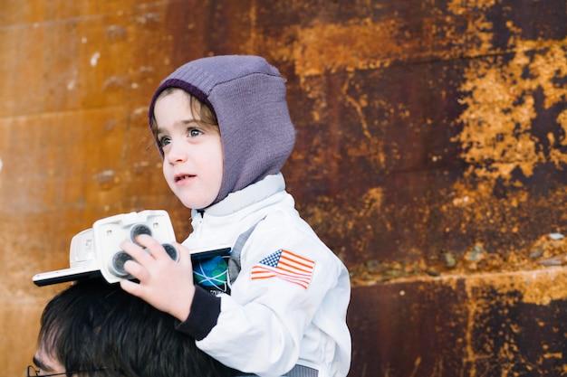 Menina em traje espacial sentado no pai