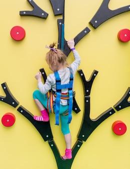 Menina em trens de seguros na parede de escalada