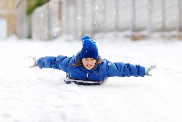 Menina em tubos de neve ladeira abaixo no dia de inverno