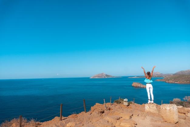 Menina em um alto penhasco acima do mar
