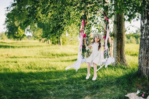 Menina em um balanço decorado com fitas e flores na natureza em um dia ensolarado de verão
