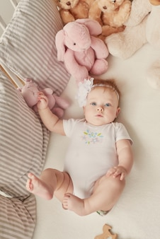 Menina em um berço com brinquedos no quarto das crianças