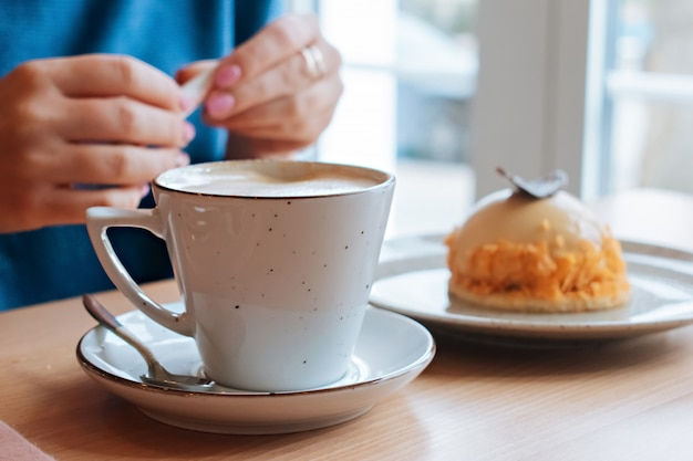 Menina em um café com café e bolo
