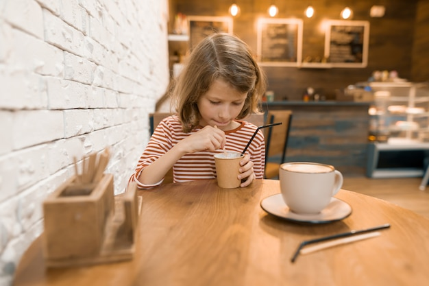 Menina em um café com uma bebida de leite