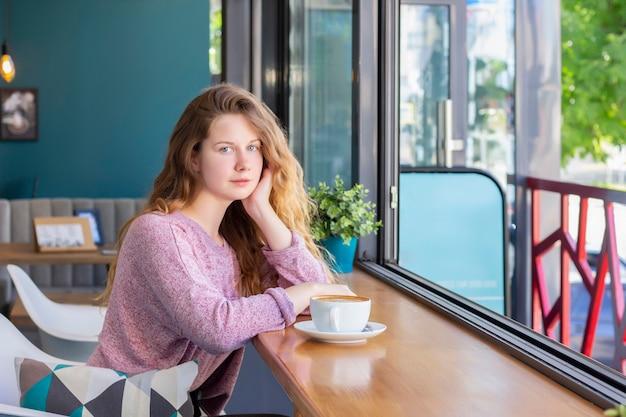 Menina em um café com uma xícara de café, sorrindo.