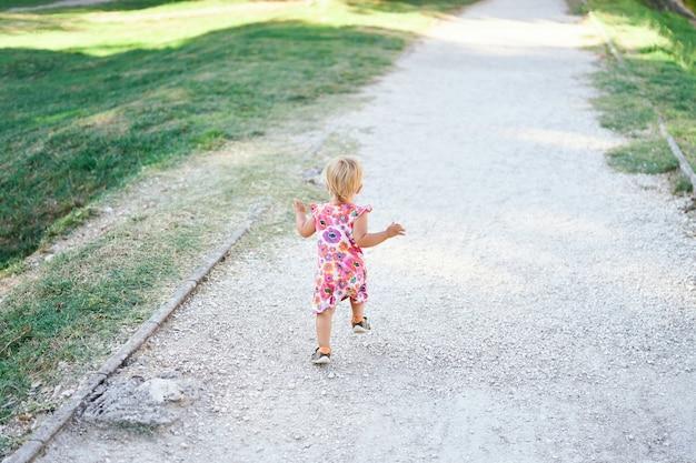 Menina em um caminho de cascalho em um gramado verde