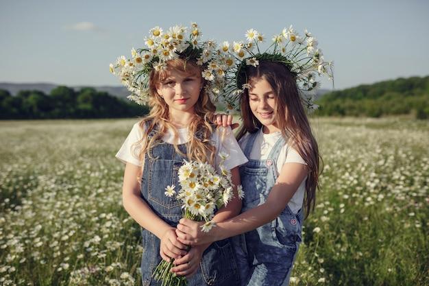 Menina em um campo de flores margarida. meninas em uma coroa de margaridas brancas, o conceito e a ideia de uma infância feliz