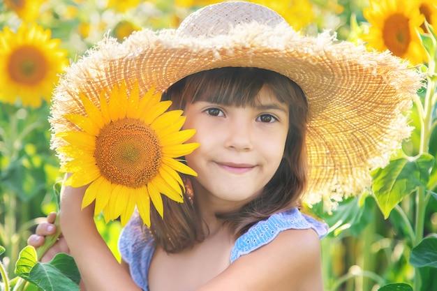 Menina em um campo de girassóis florescendo