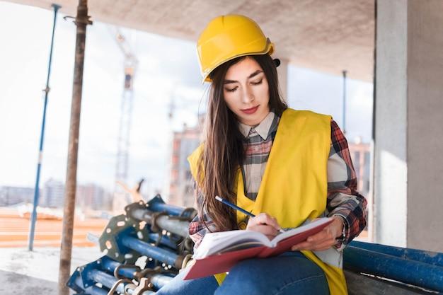 Menina em um capacete de construção e colete escreve em um caderno em uma construção