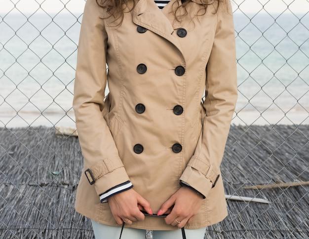 Menina em um casaco bege na costa