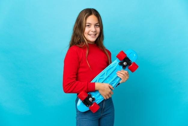 Menina em um fundo azul isolado com um skate e uma expressão feliz