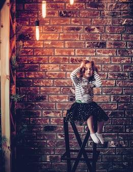 Menina em um fundo de parede de tijolos