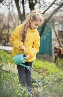 Menina em um jardim com regador verde