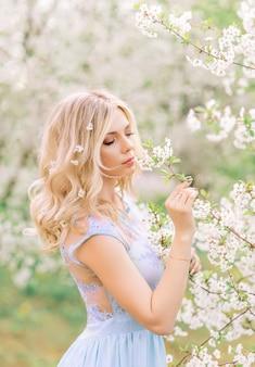 Menina em um jardim de primavera, admirando as flores. retrato no perfil. flores no seu cabelo
