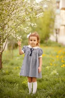 Menina em um jardim florescendo.