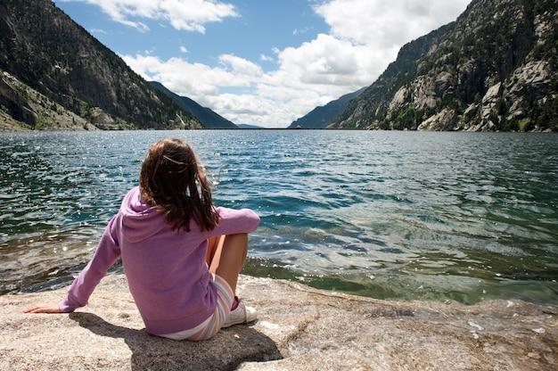 Menina em um lago de montanha