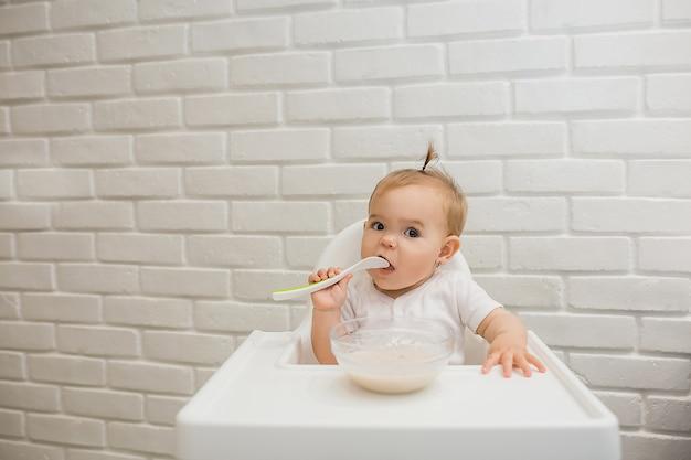 Menina em um macacão branco está sentada em uma cadeira de alimentação com uma colher