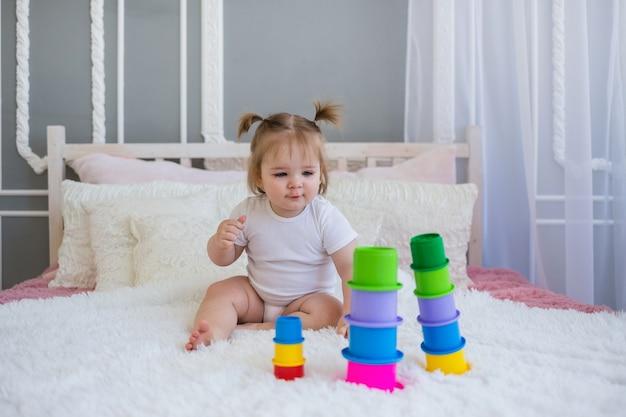 Menina em um macacão branco se senta na cama e brinca com um brinquedo de pirâmide no quarto