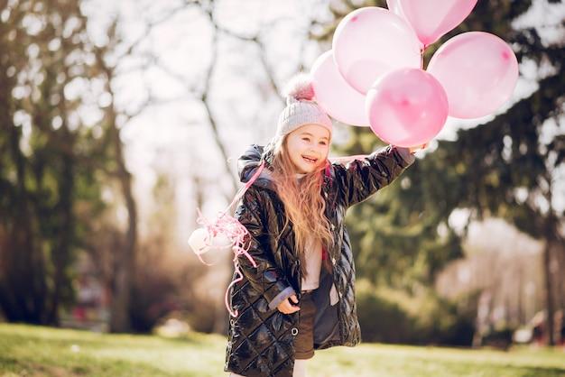 Menina em um parque brincando em uma grama
