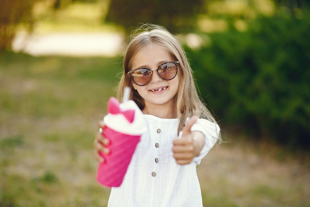Menina em um parque em pé com copo rosa